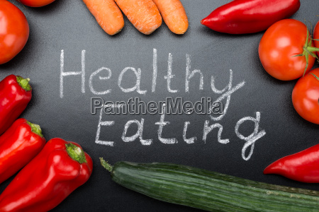healthy eating written amidst vegetables on