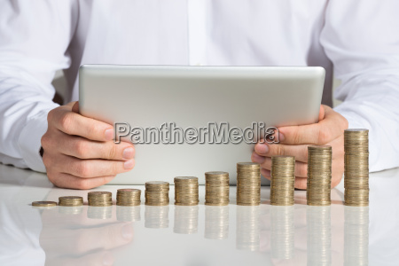 businessman using digital tablet with stacked