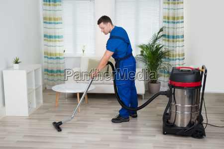 arbeiter reinigungsboden mit staubsauger zu hause