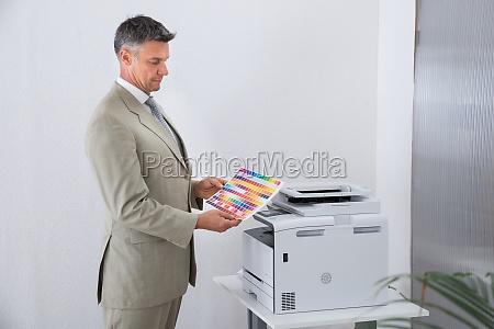 geschaeftsmann der bunt papier von farbdrucker