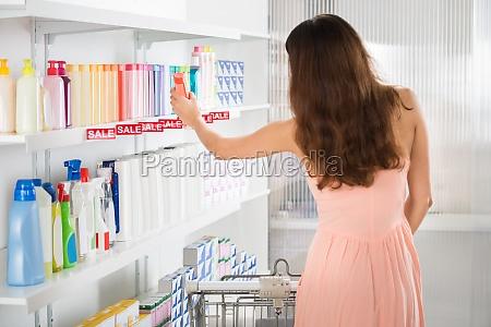frau mit einkaufswagen kauf beauty produkte