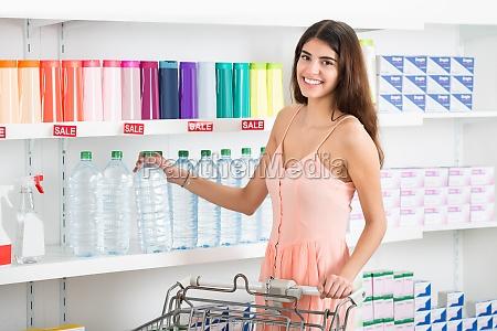 happy woman buying flasche mineralwasser im