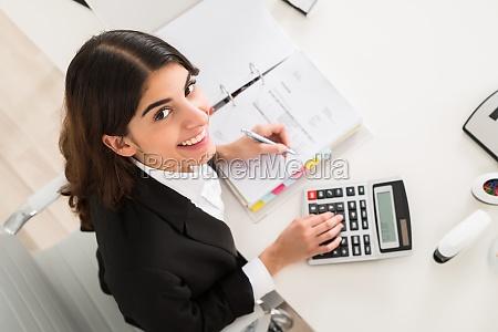 glueckliche geschaeftsfrau die am schreibtisch finanzielle