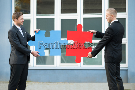 businessmen joining jigsaw pieces outside office