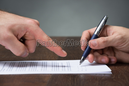 businessman pointing partner to sign agreement