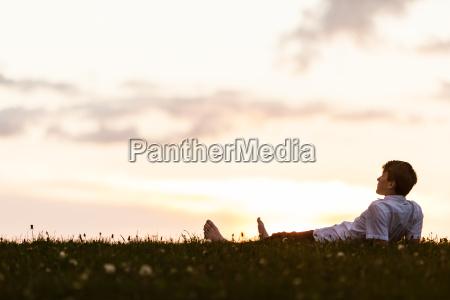 barefoot young man lying watching the