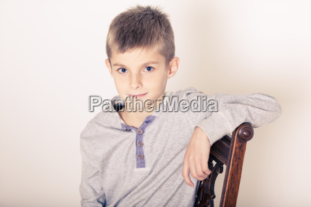 seated cute boy leaning arm on
