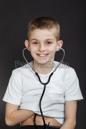 smiling boy checking his heart with