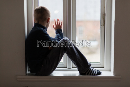 junge auf einem fensterbrett sitzen winken