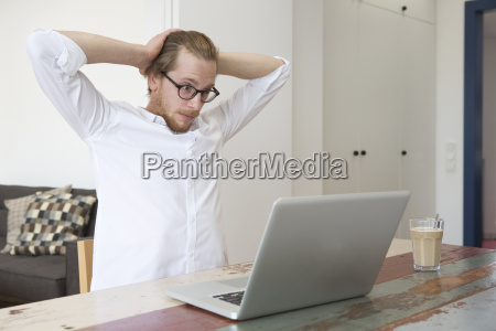 young man sitting with his laptop