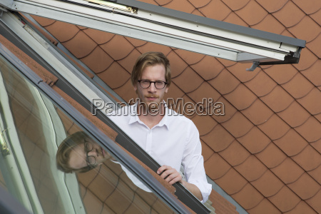 junger mann schaut aus einem dachfenster