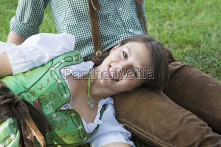 bayerisches paar sitzt auf dem rasen