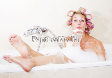 frau mit lockenwickler in der badewanne