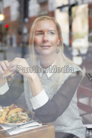woman with burger looking through window