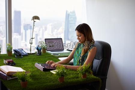 environmentalist woman types email with tablet