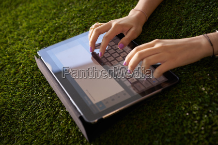woman emailing and texting with tablet