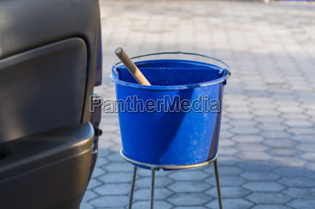 blauer eimer mit wasser an einer