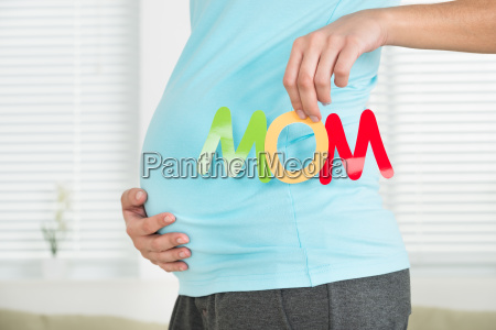 midsection of pregnant woman holding word