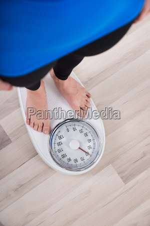 woman measuring weight on weighing scale