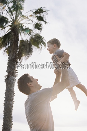 man standing by a palm tree