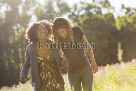 two women walking through a field
