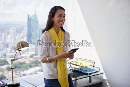 latina business woman text messaging on