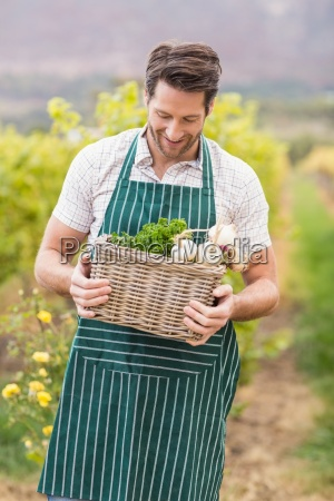 young happy farmer holding a basket