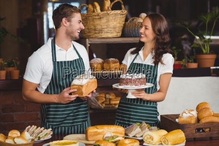 smiling co workers showing bread and