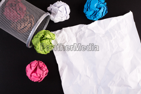 creased color papers and office bin