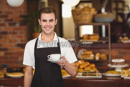 smiling barista holding cup of coffee
