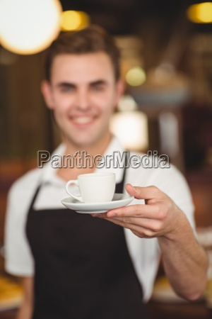 smiling barista offering cup of coffee