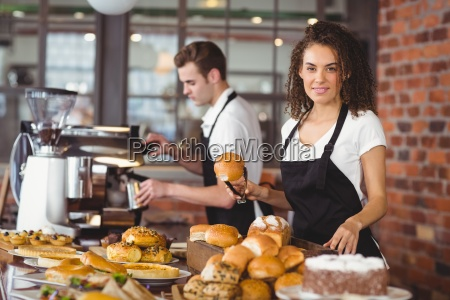 smiling waitress holding bread roll with