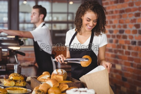 smiling waitress putting bread roll in