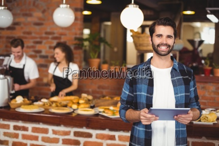 smiling hipster using tablet in front
