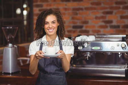 smiling barista showing cup of coffee