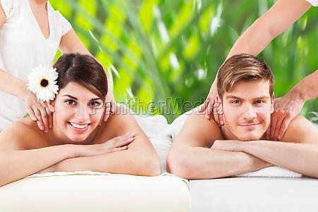 glueckliche junge paare empfangen schulter massage