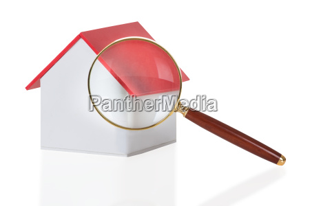 closeup of magnifying glass and house