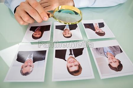 person mit candidate fotografie und vergroesserungsglas
