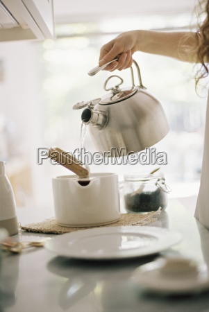 woman standing in a kitchen pouring