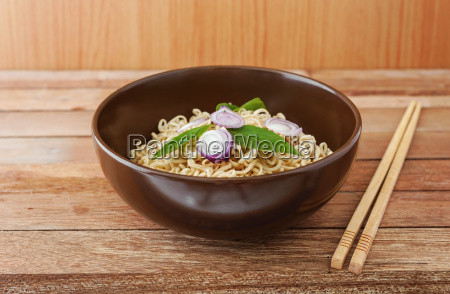noodle in brown bowl with wooden