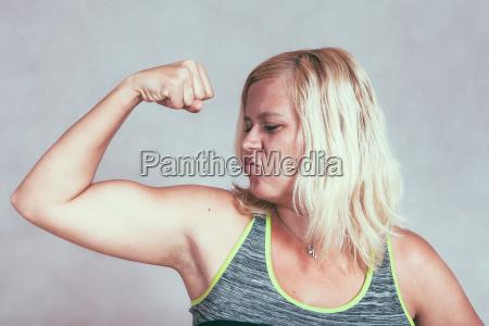 starke muskel sportliche frau beugen bizeps