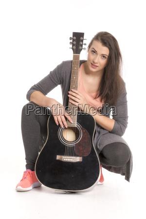 junge frau mit gitarre sitzt auf