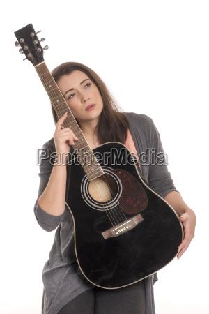 schoene frau mit gitarre schaut sinnlich