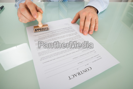 businessman stamping on contract form