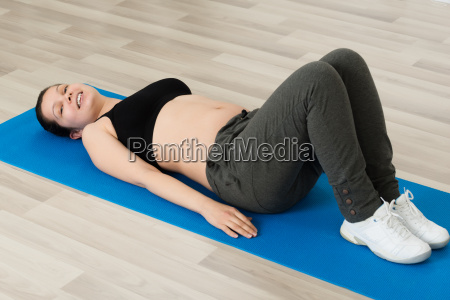 pregnant woman lying on exercise mat