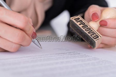 businessperson hand with pen and stamp