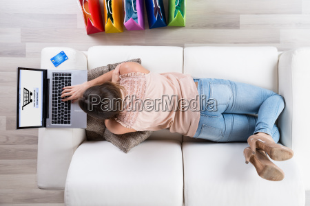woman on sofa shopping online with