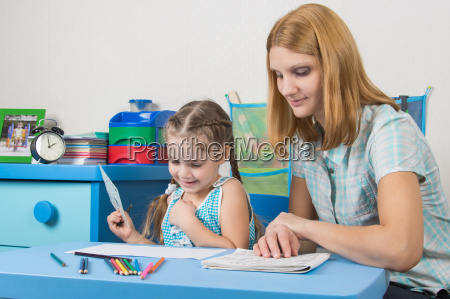girl enjoys painting with teacher in