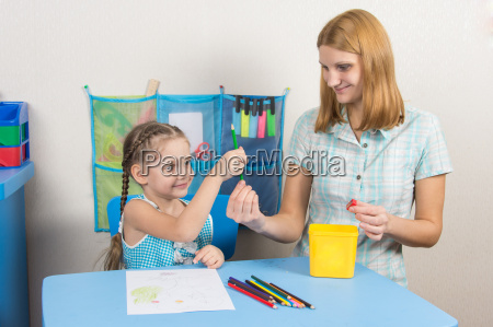 five year girl takes pencil from