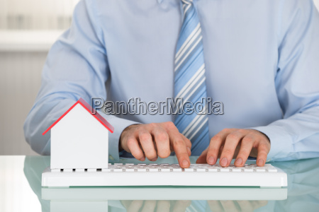 businessman with house model and keyboard